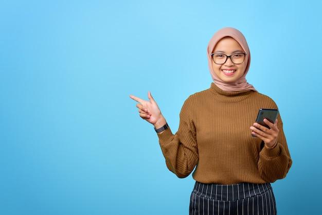 Fijne jonge aziatische vrouw die een mobiele telefoon vasthoudt en met de vinger wijst om ruimte op een blauwe achtergrond te kopiëren