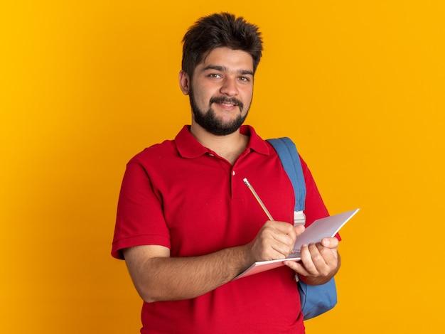 Fijne jonge, bebaarde student in een rood poloshirt met rugzak met een notitieboekje en potlood die vrolijk lacht en over de oranje muur staat
