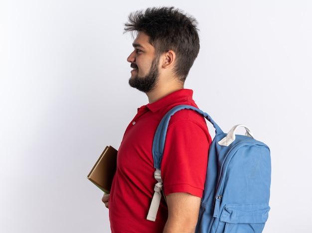 Fijne jonge, bebaarde student in een rood poloshirt met rugzak met notitieboekjes die zijwaarts over een witte muur staan