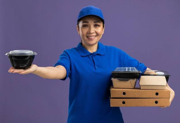 Fijne jonge bezorger in blauw uniform en pet met pizzadozen en voedselpakketten die vrolijk glimlachen over de paarse muur
