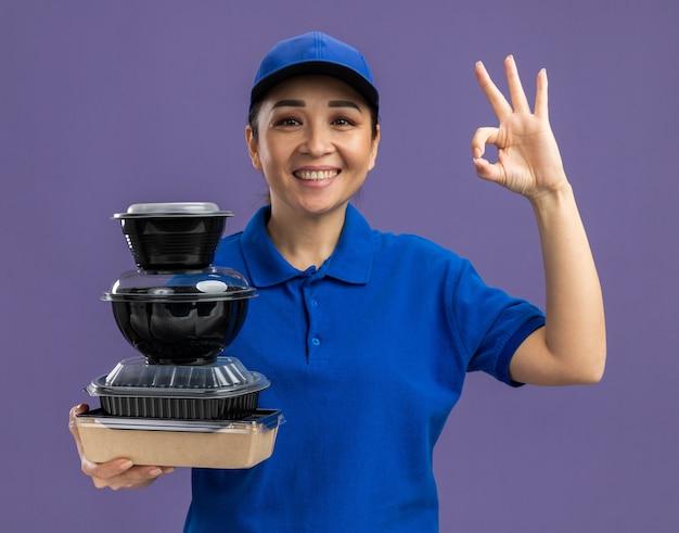 Fijne jonge bezorgvrouw in blauw uniform en pet met een stapel voedselpakketten die vrolijk lacht met een goed teken