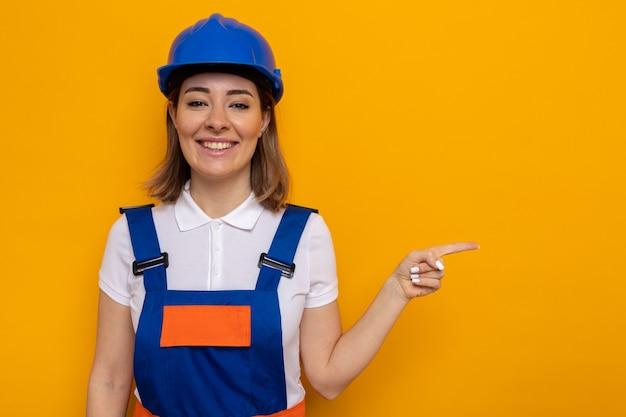 Fijne jonge bouwvrouw in bouwuniform en veiligheidshelm die vrolijk glimlachend met de wijsvinger naar de zijkant wijst