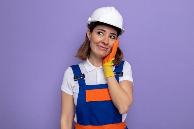 Fijne jonge bouwvrouw in bouwuniform en veiligheidshelm in rubberen handschoenen die opzij kijkt en glimlachend haar wang aanraakt