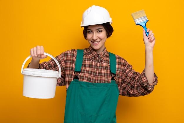 Fijne jonge bouwvrouw in bouwuniform en veiligheidshelm met verfemmer en borstel die vrolijk glimlacht over de oranje muur