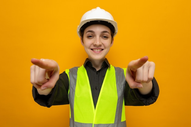 Fijne jonge bouwvrouw in bouwvest en veiligheidshelm glimlachend zelfverzekerd wijzend met wijsvingers die op oranje staan