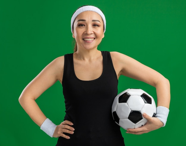 Fijne jonge fitnessvrouw met hoofdband en armbanden die voetbal vasthoudt met een glimlach op het gezicht over een groene muur