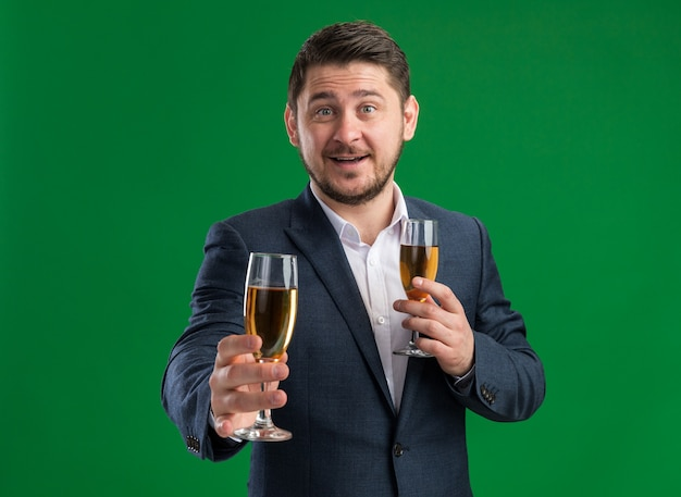 Fijne jonge knappe man met een pak met glazen champagne die valentijnsdag gaat vieren met een glimlach op het gezicht over de groene muur