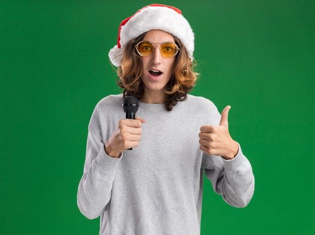 Fijne jonge man met een kerstmuts en een gele bril met een microfoon die vrolijk lacht en zijn duimen opsteekt terwijl hij over de groene muur staat