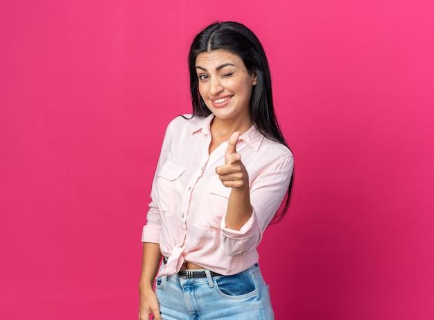 Fijne jonge mooie vrouw in vrijetijdskleding die lacht en knipoogt, wijzend met de wijsvinger aan de voorkant die over de roze muur staat