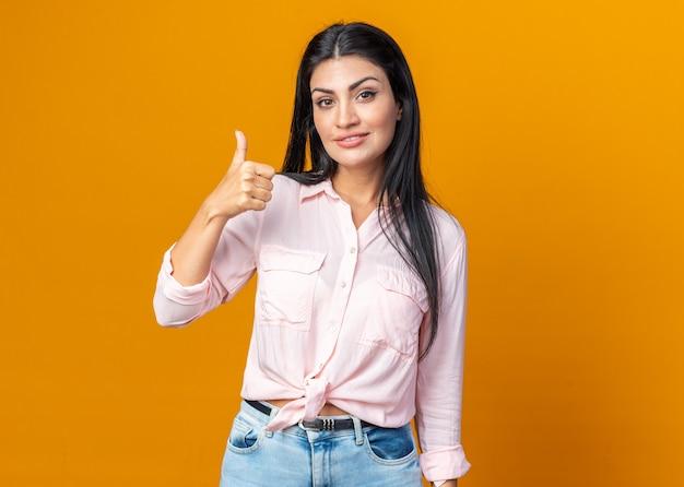 Fijne jonge mooie vrouw in vrijetijdskleding die naar de voorkant kijkt en zelfverzekerd glimlacht en duimen laat zien die over de oranje muur staan