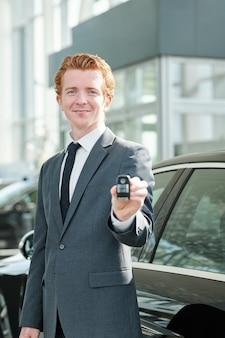 Fijne jonge succesvolle verkoper van auto's in het autocentrum die een alarmsysteem op afstand aan de koper toont terwijl hij op een zwart voertuig staat