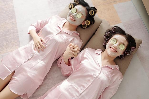 Fijne jonge vrouwen in lichtroze zijden pyjama's die elkaars hand vasthouden als ze op de vloer liggen met opheffende en verstevigende maskers en plakjes komkommer op