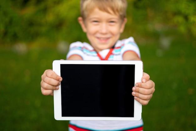 Fijne kleine babyjongen houdt een tabletcomputer buiten in een zomerpark, close-up van kinderhanden