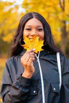 Fijne mooie jonge afro-amerikaanse vrouw met een glimlach in een modieus zwart casual jasje bedekt haar lippen met geel herfstblad op de natuur