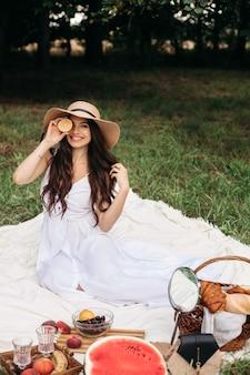 Fijne mooie vrouw die een hoed met rand en een witte jurk draagt terwijl ze staat en een broodmand vasthoudt in het zomerpark