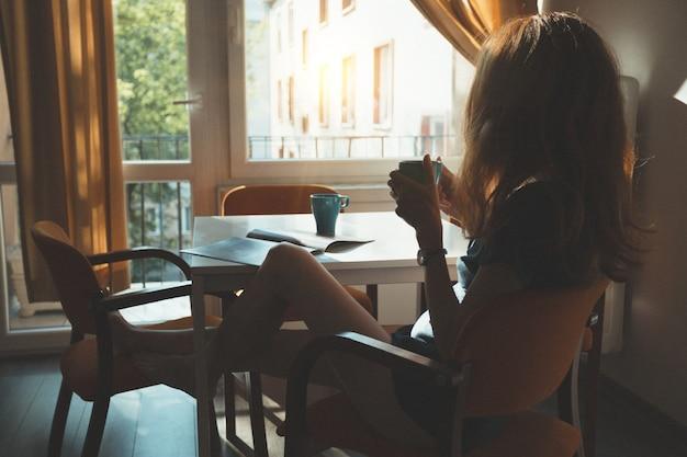 Fijne ochtend - het meisje zit in de keuken en drinkt de ochtendkoffie