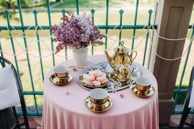 Fijne ochtendtheetafel met lila bloemen, antieke lepels en schaaltjes op een tafel met een roze tafelkleed.