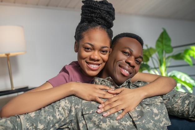 Fijne ontmoeting. afro-amerikaanse glanzende vrouw knuffelen jonge aantrekkelijke man in militair uniform blij thuis op de bank
