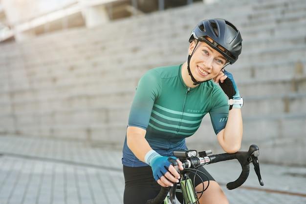 Fijne professionele vrouwelijke wielrenner in beschermende kleding die naar de camera glimlacht terwijl ze met haar fiets staat