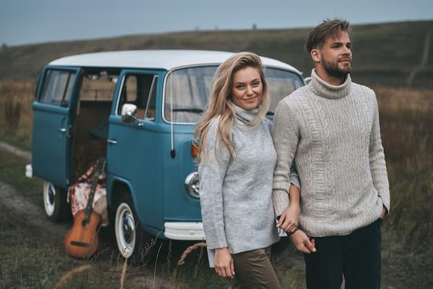 Fijne reis. mooie jonge paar hand in hand en glimlachen terwijl ze in de buurt van de blauwe retro-stijl minibusje staan