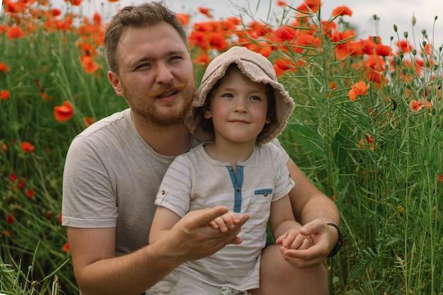 Fijne vaderdag kleine jongen en vader spelen in een prachtig veld met rode klaprozen