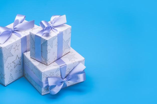 Fijne vakantie. geschenkdozen met patronen, lila lint met strik op blauwe ruimte. nieuwjaar en kerstsfeer.