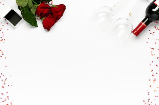 Fijne valentijnsdag. bos van rode rozen met geschenkdoos voor ring, fles wijn en glazen met confetti op wit