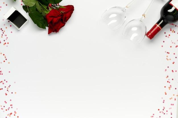Fijne valentijnsdag. bos van rode rozen met geschenkdoos voor ring, fles wijn en glazen met confetti op witte achtergrond