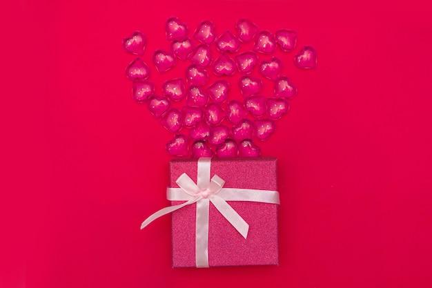 Fijne valentijnsdag flatlay. bovenaanzicht huidige geschenkdoos, harten op gele kleur van de achtergrond van het jaar 2021. valentijnsdag of nieuwjaar wenskaart. panton