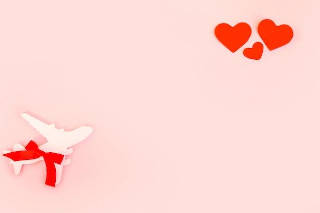 Fijne valentijnsdag. het vliegtuig van kinderen op een roze achtergrond met rood hart