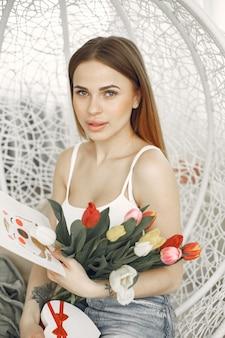 Fijne valentijnsdag. jonge dame zit in een stoel met tulpen en wenskaart.