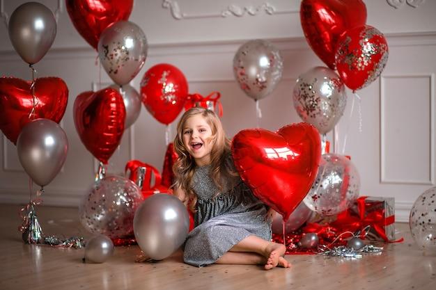 Fijne valentijnsdag! schattig meisje in een rode jurk met ballonnen en confetti