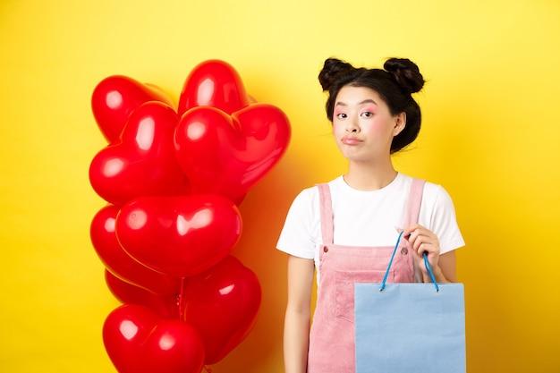 Fijne valentijnsdag. stijlvol aziatisch enkel meisje dat zichzelf cadeau koopt, boodschappentas vasthoudt en onaangedaan naar de camera kijkt, staande over gele achtergrond.