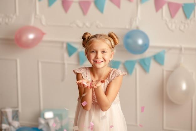 Fijne verjaardag. portret van een gelukkig schattig blond meisje in een feestelijk decor met confetti.
