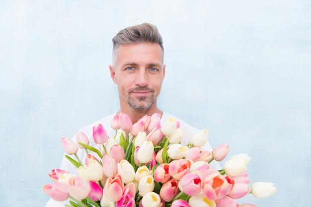 Fijne vrouwendag. voor iemand speciaal. man met tulpen boeket. knappe kerel die roze bloemen houdt. aantrekkelijke man met bloemen. man draagt cadeau voor valentijnsdag of verjaardag. bloemen winkel.