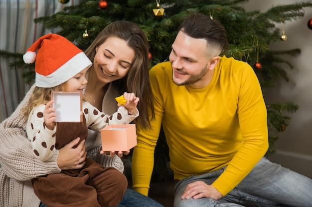 Fijne wintervakantie en prettige kerstdagen, vader, moeder en dochtertje wisselen geschenken uit in de buurt van dennenboom. oudejaarsfamilie thuis.