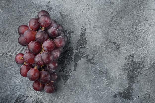 Fijnste natuurlijke tros druiven, donkerrood fruit, op grijze stenen tafel, bovenaanzicht plat