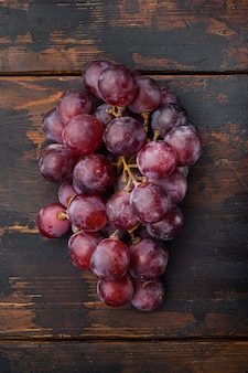 Fijnste natuurlijke tros druiven, donkerrood fruit, op oude donkere houten tafel, bovenaanzicht plat