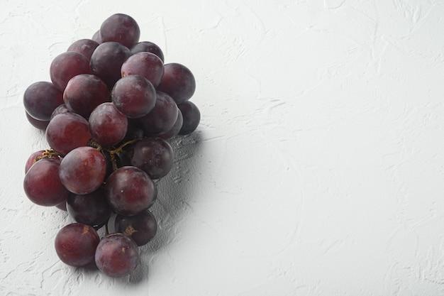 Fijnste natuurlijke tros druiven, donkerrood fruit, op witte stenen tafel