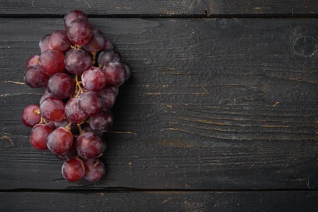 Fijnste natuurlijke tros druiven, donkerrood fruit, op zwarte houten tafel, bovenaanzicht plat