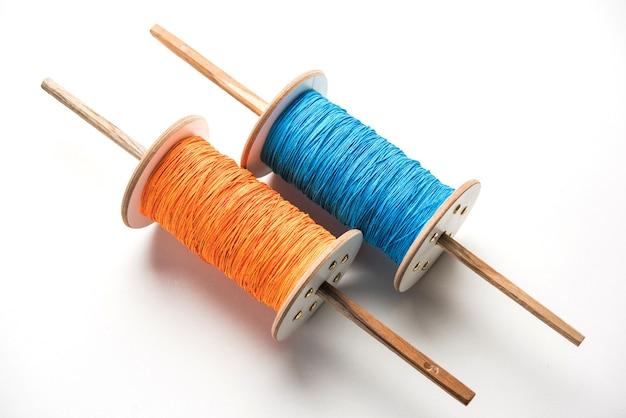 Fikri or reel ook bekend als chakri or spool met kleurrijke draad of manjha, gebruikt voor vliegeren. over witte achtergrond, selectieve focus
