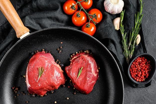 Filet mignon steak in een koekenpan. ossenhaas. zwarte muur. bovenaanzicht