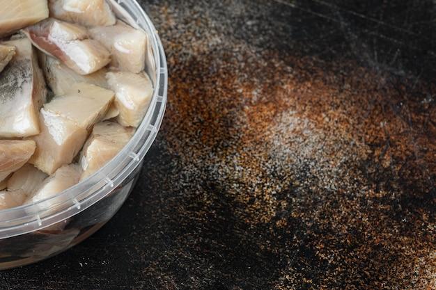 Filet van gezouten hollandse haring in olie, op oude donkere rustieke tafel