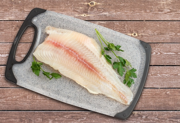 Filet van rauwe pangasius vis met peterselie bladeren op een snijplank en houten planken. bovenaanzicht.