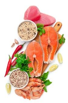 Filet van tonijn en zalm. garnaal. op een houten plank. gegarneerd met kruiden en specerijen. ernaast staan kopjes wilde rijst en quinoa. witte achtergrond. geïsoleerd. detailopname. uitzicht van boven.