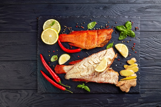 Filet van warm gerookte rode snappers op een zwarte stenen plaat met specerijen, kruiden en gesneden citroenen, weergave van bovenaf, close-up