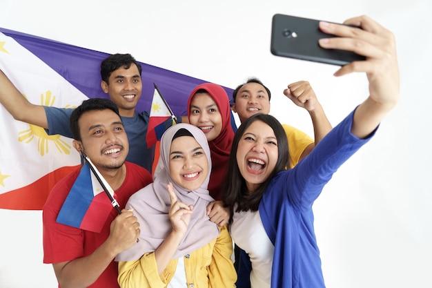 Filipijnse supporter die selfie neemt en de vlag van filippijnen houdt tijdens de onafhankelijkheid