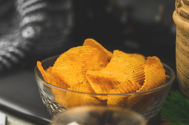 Film kijken alleen thuis, ongezond eten, snack, chips in kom, laptop, gezellige winterachtergrond. hoge kwaliteit foto