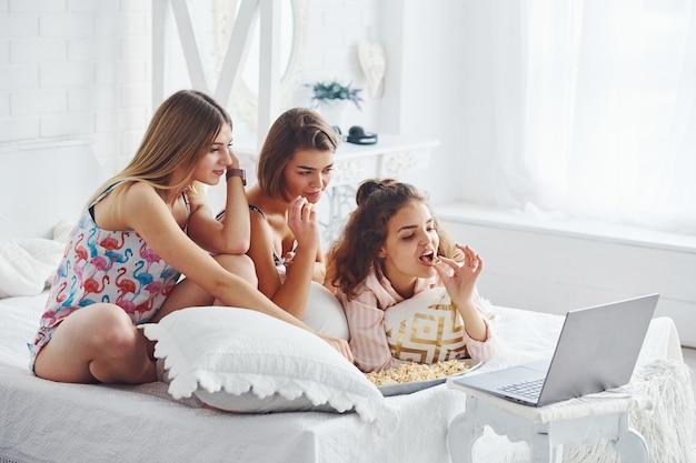 Film kijken en popcorn eten. gelukkige vrouwelijke vrienden die plezier hebben op een pyjamafeestje in de slaapkamer.