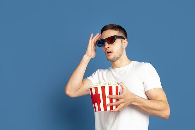 Film kijken met popcorn. portret van een blanke jongeman op blauwe studiomuur.